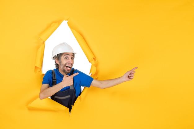 Vooraanzicht mannelijke bouwer in uniform op gele bureaukleur constructeur gebouw architectuur baan structuur werknemer