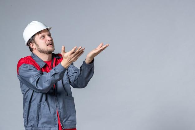 Vooraanzicht mannelijke bouwer in uniform op lichte achtergrond
