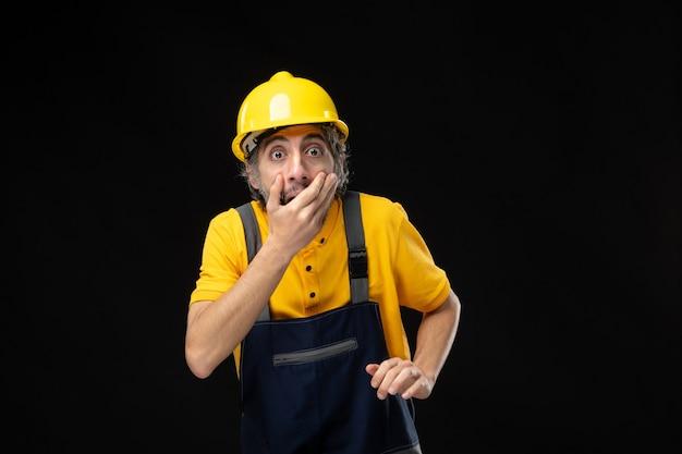 Vooraanzicht mannelijke bouwer in uniform op zwarte muur