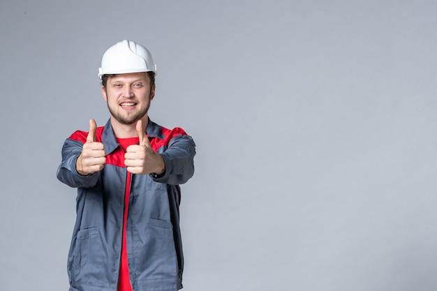 Vooraanzicht mannelijke bouwer in uniform verrukt op lichte achtergrond