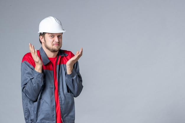 Vooraanzicht mannelijke bouwer in uniform verward op lichte achtergrond