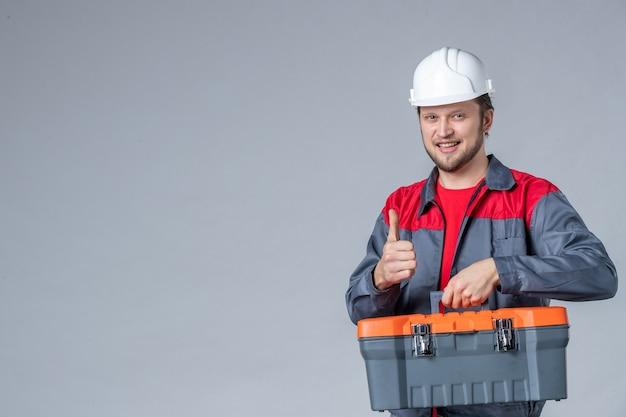 Vooraanzicht mannelijke bouwer in uniforme gereedschapskoffer met glimlach op grijze achtergrond