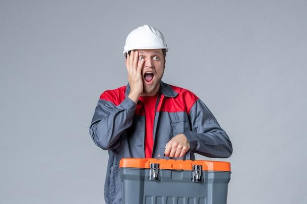 Vooraanzicht mannelijke bouwer in uniforme gereedschapskoffer met opgewonden gezicht op grijze achtergrond