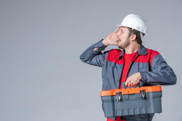 Vooraanzicht mannelijke bouwer in uniforme gereedschapskoffer op grijze achtergrond Gratis Foto
