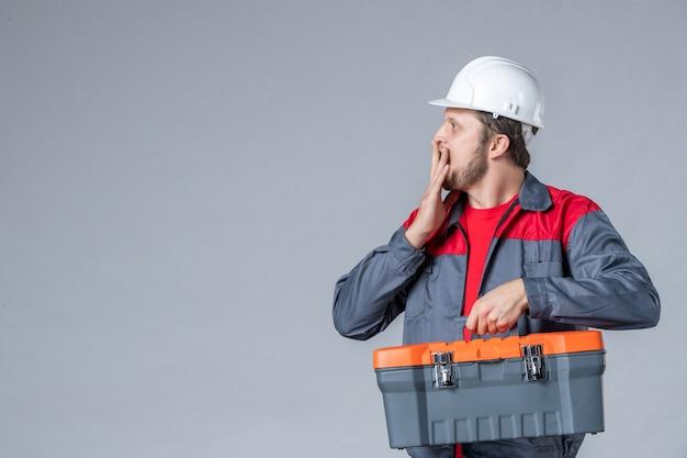 Vooraanzicht mannelijke bouwer in uniforme gereedschapskoffer op grijze achtergrond