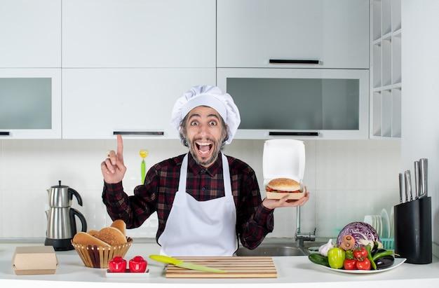 Vooraanzicht mannelijke chef-kok die hamburger omhoog houdt wijzend op plafond in de keuken