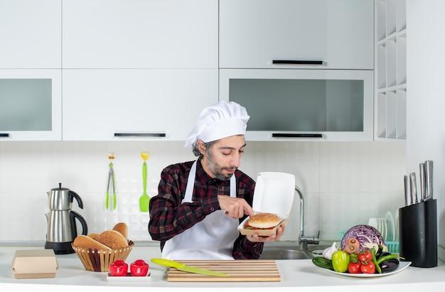 Vooraanzicht mannelijke chef-kok houdt hamburger in de keuken