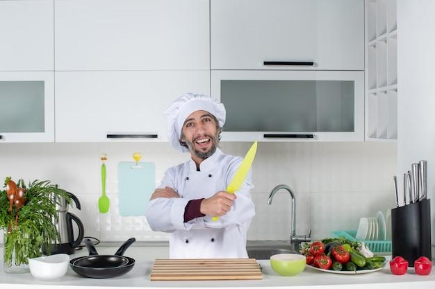 Vooraanzicht mannelijke chef-kok in uniform die mes omhoog houdt die handen kruisen op moderne keuken