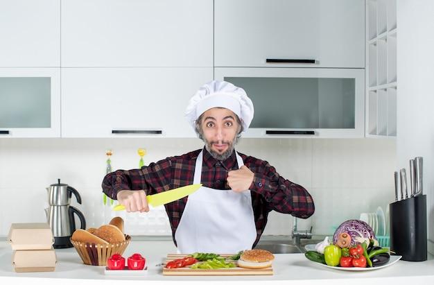 Vooraanzicht mannelijke chef-kok met mes in de keuken