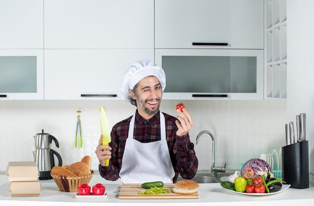 Vooraanzicht mannelijke chef-kok met tomaat en mes in de keuken