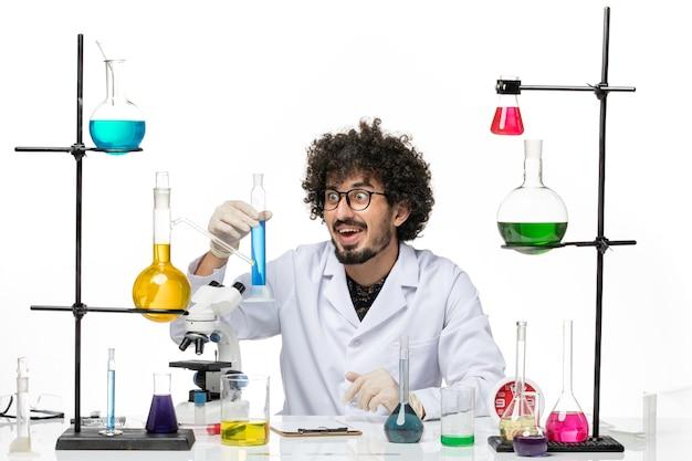 Vooraanzicht mannelijke chemicus die in medisch kostuum blauwe oplossing op wit bureau houdt