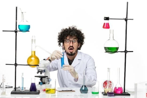 Vooraanzicht mannelijke chemicus in medisch pak blauwe oplossing op witte ruimte te houden