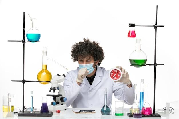 Vooraanzicht mannelijke chemicus in medisch pak en met masker die rode klokken houden die op witte ruimte hoesten