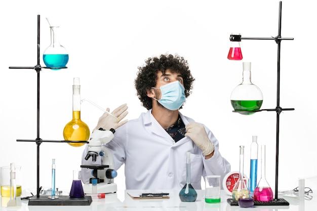 Vooraanzicht mannelijke chemicus in medisch pak en met masker gewoon zittend met oplossingen op de lichte witte ruimte