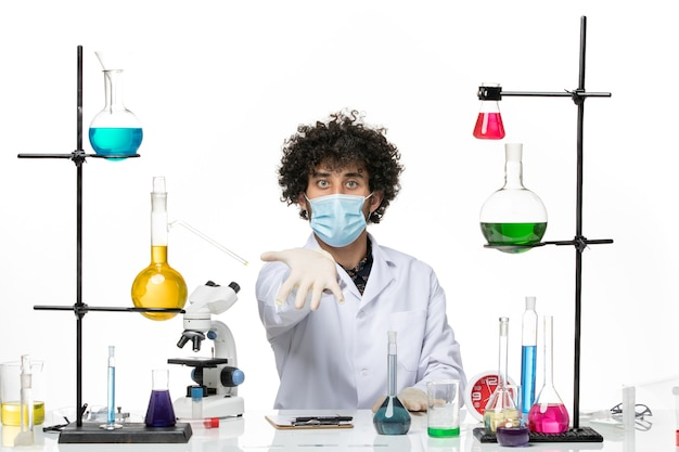 Vooraanzicht mannelijke chemicus in medisch pak en met masker gewoon zittend met oplossingen op witte ruimte