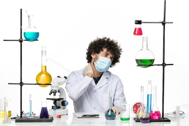 Vooraanzicht mannelijke chemicus in medisch pak en met masker met nekpijn op witte ruimte