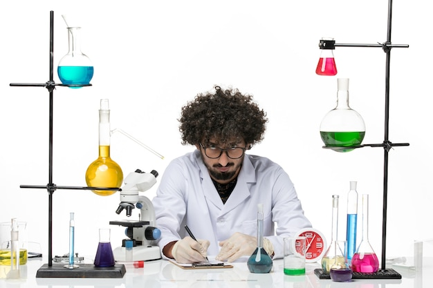 Vooraanzicht mannelijke chemicus in medisch pak notities op witte ruimte opschrijven