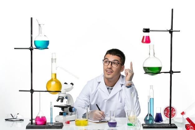 Vooraanzicht mannelijke chemicus in medisch pak zitten en schrijven iets op wit bureau virus covid splash ziekte wetenschap