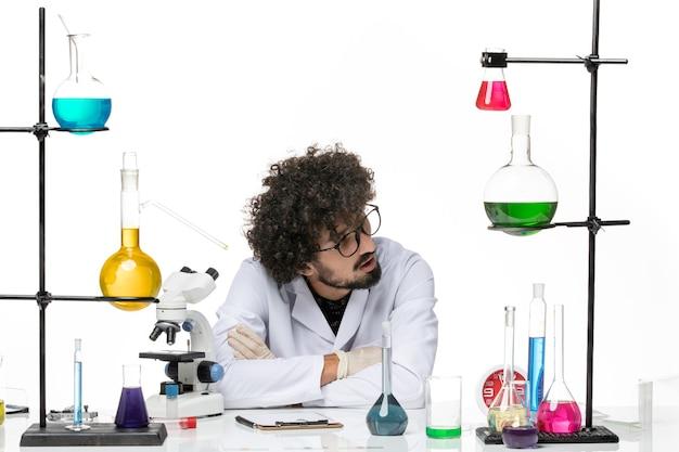 Vooraanzicht mannelijke chemicus in medisch pak zittend op witte ruimte
