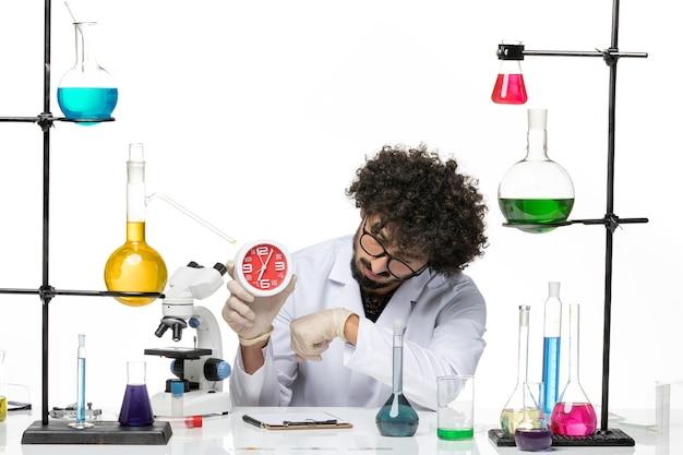 Vooraanzicht mannelijke chemicus in medische pak klokken op witte ruimte te houden