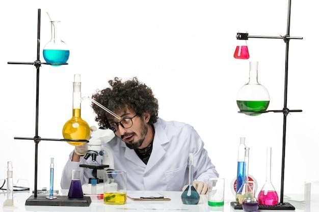 Vooraanzicht mannelijke chemicus in medische pak met behulp van microscoop op witte ruimte