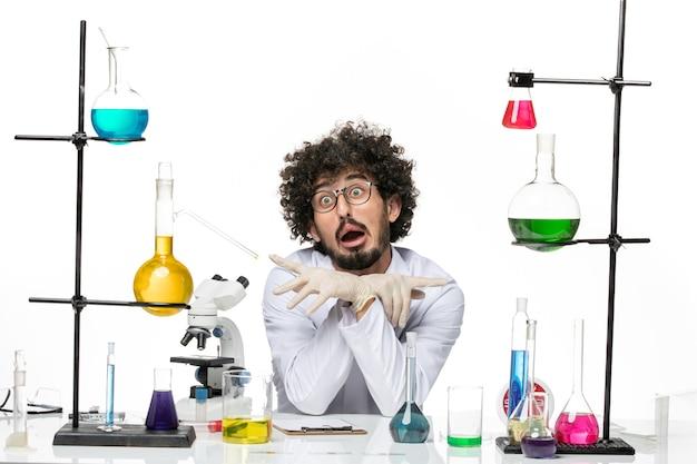 Vooraanzicht mannelijke chemicus in medische pak zit gewoon tafel met oplossingen op lichte witte ruimte