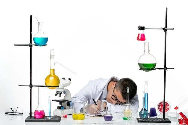 Vooraanzicht mannelijke chemicus in medische pak zitten en schrijven iets op lichte witte achtergrond virus covid splash ziekte wetenschap