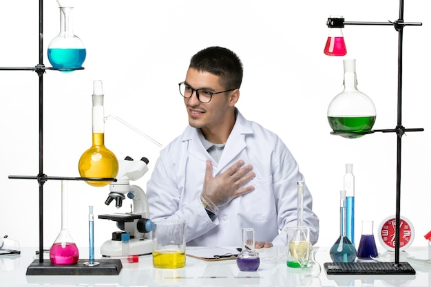 Vooraanzicht mannelijke chemicus in medische pak zittend met oplossingen op wit bureau virus covid ziekte wetenschap