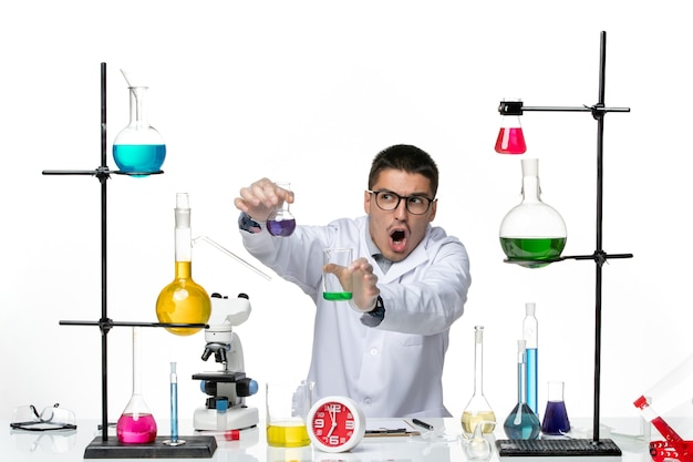 Vooraanzicht mannelijke chemicus in wit medisch pak bedrijf kolven met oplossingen op witte achtergrond virus wetenschap covid pandemie lab