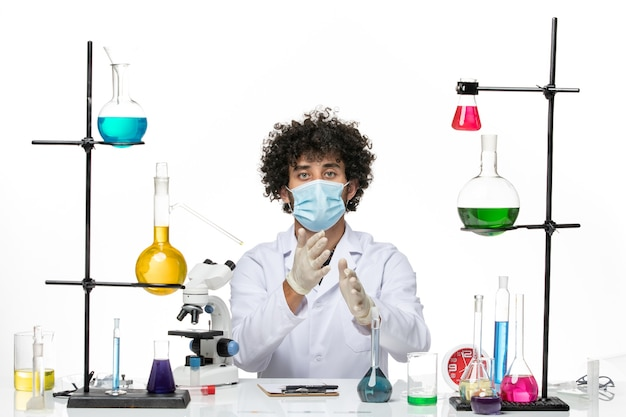 Vooraanzicht mannelijke chemicus in wit medisch pak en met masker zittend op witte ruimte