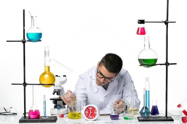 Vooraanzicht mannelijke chemicus in wit medisch pak met kolven met oplossingen op witte vloer virus wetenschap covid-pandemie lab
