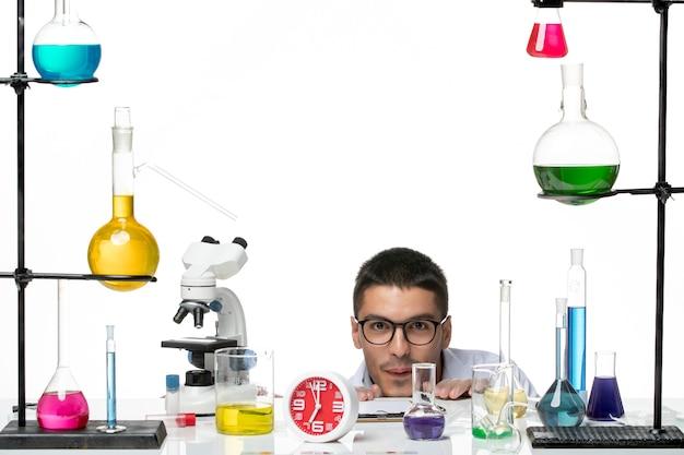Vooraanzicht mannelijke chemicus in wit medisch pak verbergen op witte achtergrond virus wetenschap covid-pandemie lab
