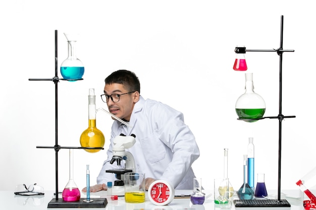 Vooraanzicht mannelijke chemicus in wit medisch pak zitten en het maken van grappige gezichten op witte achtergrond virus wetenschap covid-pandemisch lab
