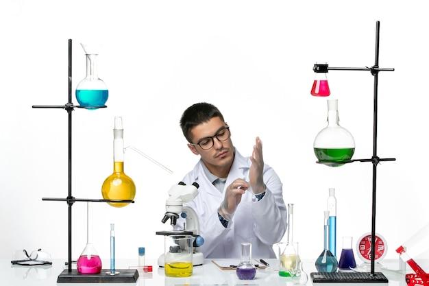 Vooraanzicht mannelijke chemicus in witte medische pak zitten met oplossingen handschoenen dragen op witte achtergrond virus lab covid ziekte wetenschap
