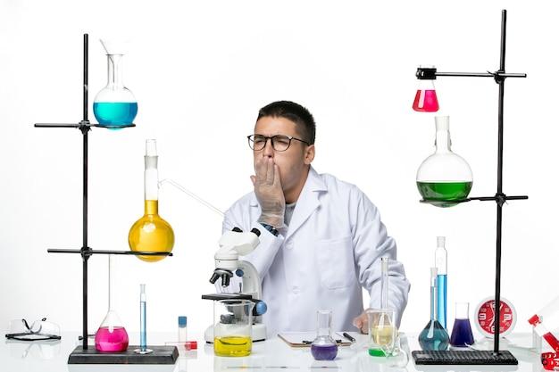 Vooraanzicht mannelijke chemicus in witte medische pak zitten met oplossingen hoesten op witte achtergrond virus lab covid ziekte wetenschap