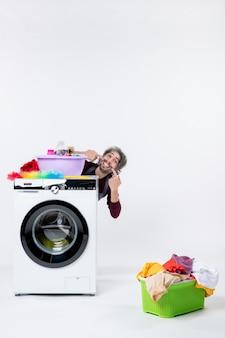 Vooraanzicht mannelijke huishoudster die zijn glimlach toont die achter de wasmand van de wasmachine op witte muur zit