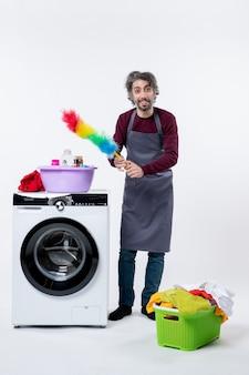 Vooraanzicht mannelijke huishoudster met plumeau die in de buurt van wasmachine op witte muur staat