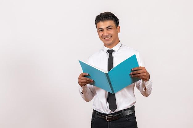 Vooraanzicht mannelijke kantoormedewerker die documenten controleert op witte bureau mannelijke zakelijke werkbaan