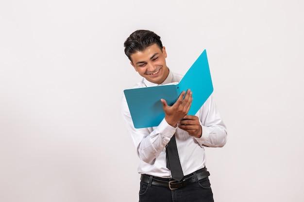 Vooraanzicht mannelijke kantoormedewerker die documenten controleert op witte muur mannelijke zakelijke werkbaan