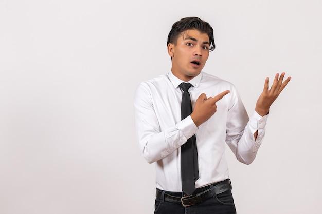 Vooraanzicht mannelijke kantoormedewerker die zich voordeed op witte muur werk mannelijke baan bedrijf