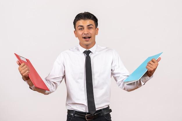 Vooraanzicht mannelijke kantoormedewerker met documenten op witte muur mannelijke zakelijke werkbaan