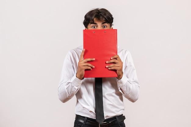Vooraanzicht mannelijke kantoormedewerker met rood bestand op witte muur kantoorwerk baan mens