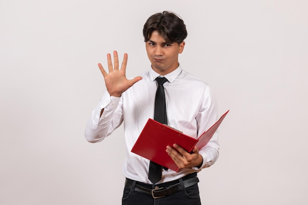 Vooraanzicht mannelijke kantoormedewerker met rood bestand op witte muur werk kantoor menselijke baan