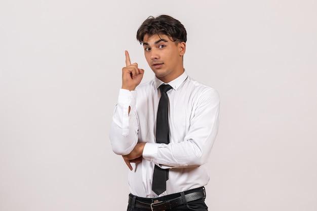 Vooraanzicht mannelijke kantoormedewerker staande op witte muur kantoorwerk baan mannelijke mens