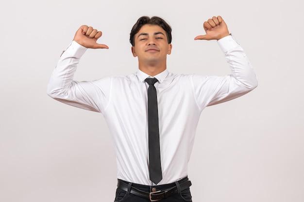 Vooraanzicht mannelijke kantoormedewerker voelt zich zelfverzekerd op witte muur menselijke kantoorwerkbaan