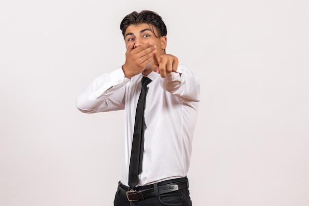 Vooraanzicht mannelijke kantoormedewerker wijzend met geschokt gezicht op witte muur werk mannelijke baan