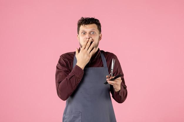 Vooraanzicht mannelijke kapper met haarborstel en schaar op roze achtergrond