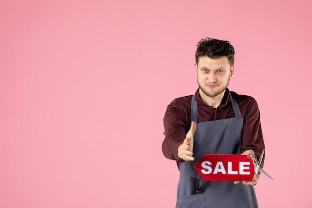 Vooraanzicht mannelijke kapper met rood verkoopnaambord op roze achtergrond