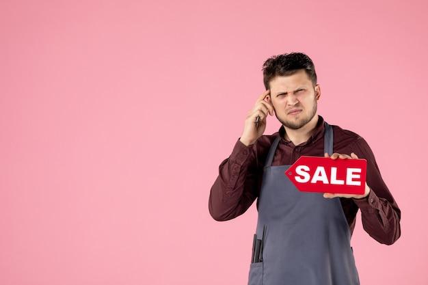 Vooraanzicht mannelijke kapper met verkoopnaambord en schaar op roze achtergrond