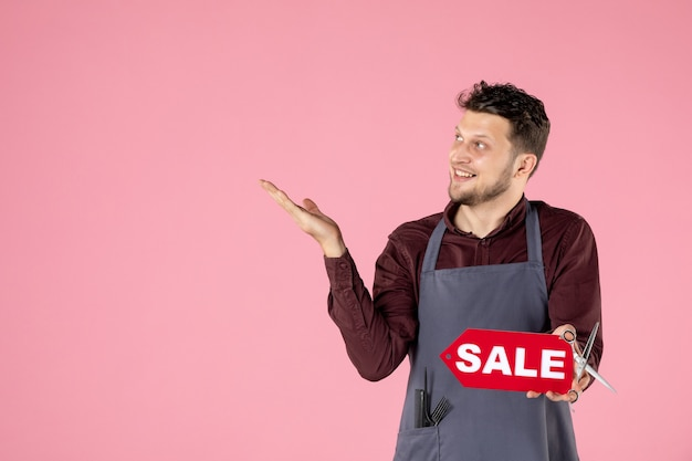 Vooraanzicht mannelijke kapper met verkoopnaambord op roze achtergrond